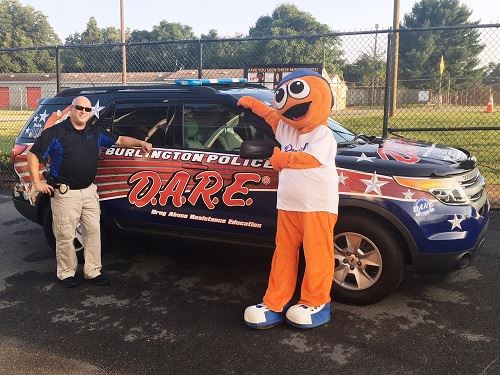 Officer Paschal stands in front of D.A.R.E. SUV with Bingo from Burlington Royals