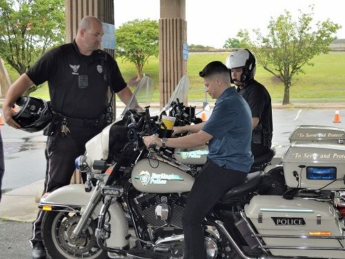 open house attendee sits on BPD motorcycle