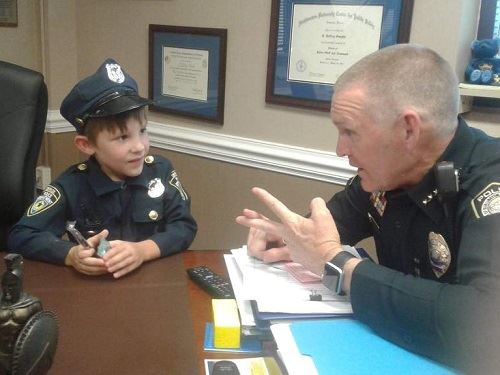 child dressed as cop talks with Chief Smythe