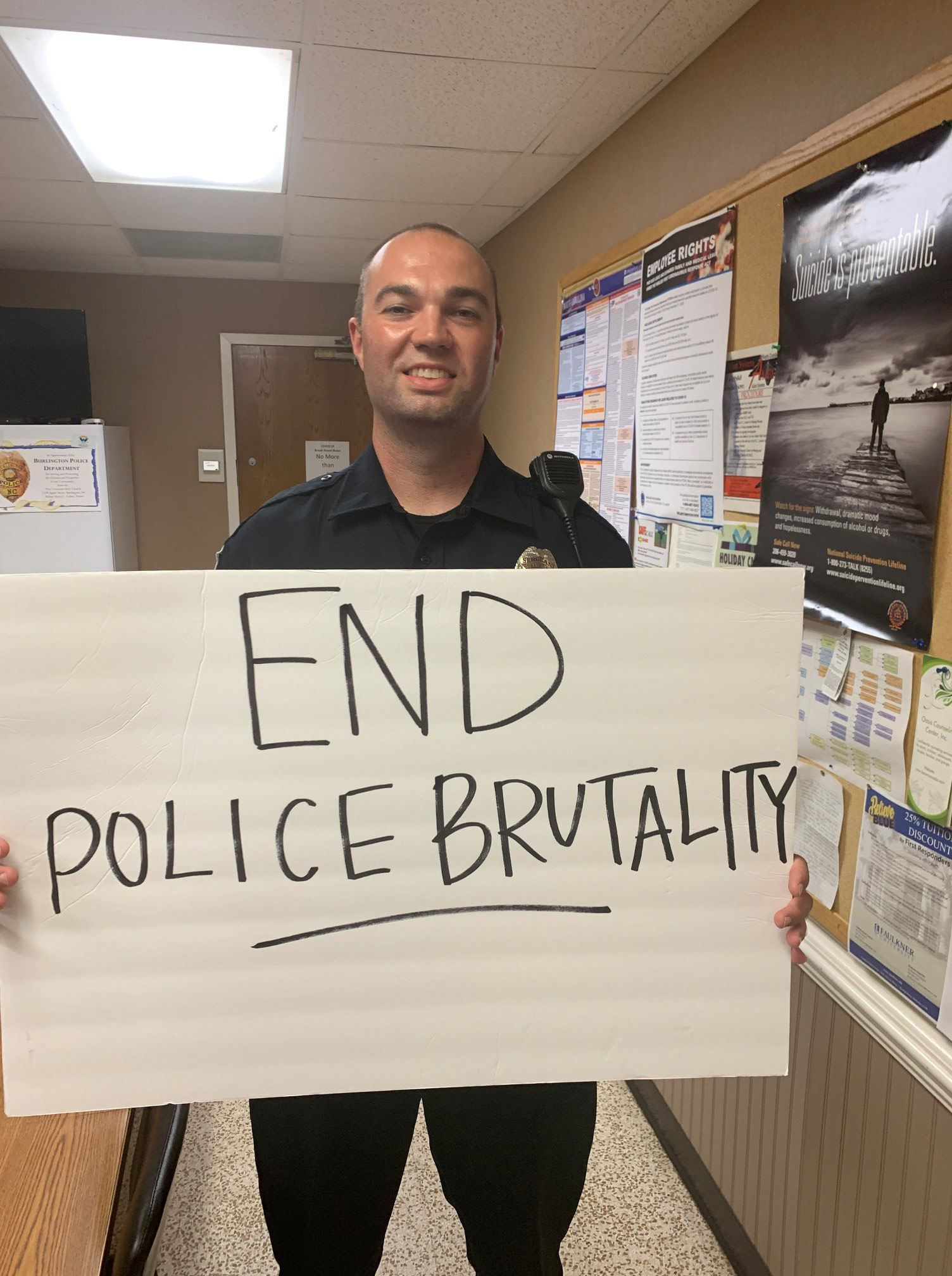 officers with end police brutality protest sign